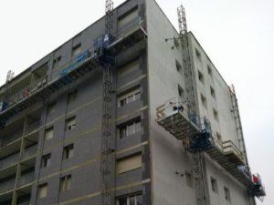 deux échafaudages mécaniques à crémaillère sur un immeuble d'habitation pour réaliser l'isolation thermique extérieure
